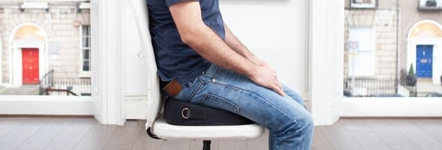 Man with jeans sitting on a foundation a posture correction wedge