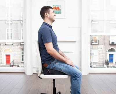 man sitting on black foundation (posture correction device)on white chair. Designed for back pain